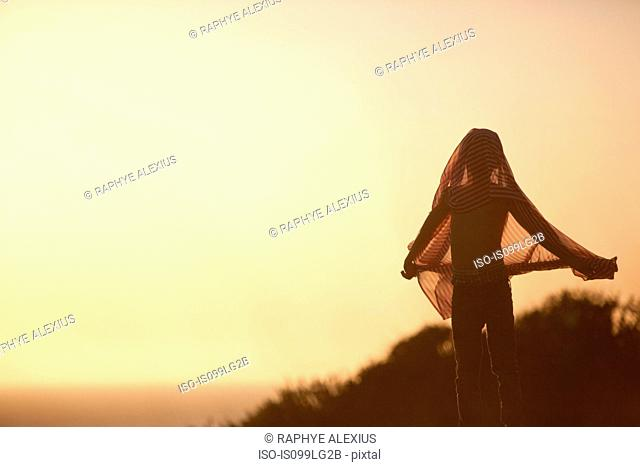 Silhouette of boy covering head with fabric