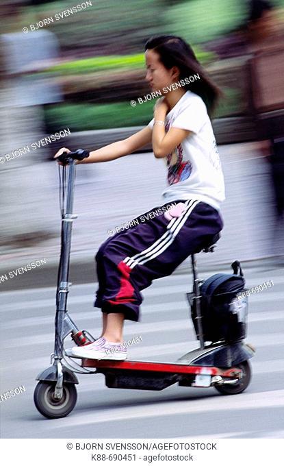 Young girl riding an electric scooter, Jinghong, Xishuangbanna, Yunnan, China
