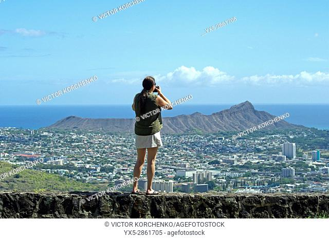 Tourist taking a picture of Dimond Head mountain and Honolulu, Hawaii