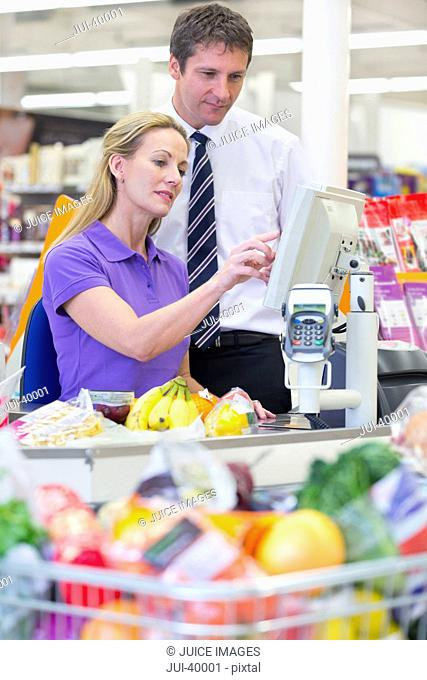 Supermarket Manager And Cashier At Checkout
