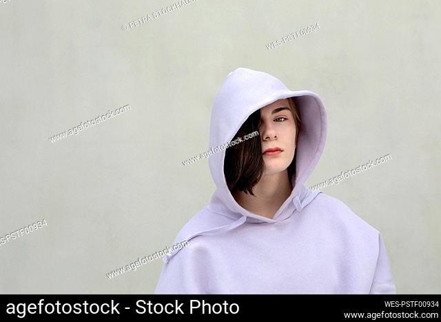 Beautiful teenage girl in hooded shirt by wall