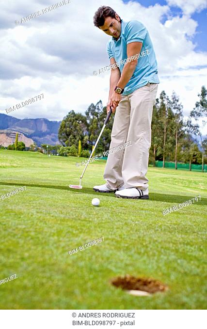 Hispanic man putting golf ball