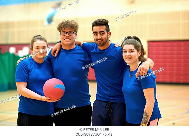 Friends on basketball court looking at camera smiling