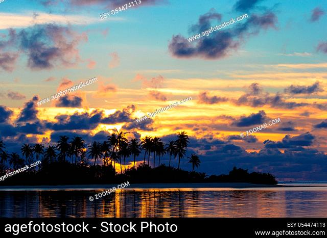 Sunset at the seaside with dark silhouettes of palm trees and amazing cloudy sky