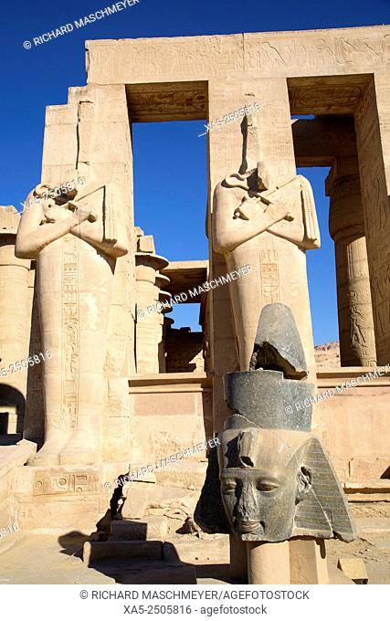 Bust of Ramses II (foreground), Statues of Osiris (background), The Ramesseum, Luxor, West Bank, Nile Valley, Egypt