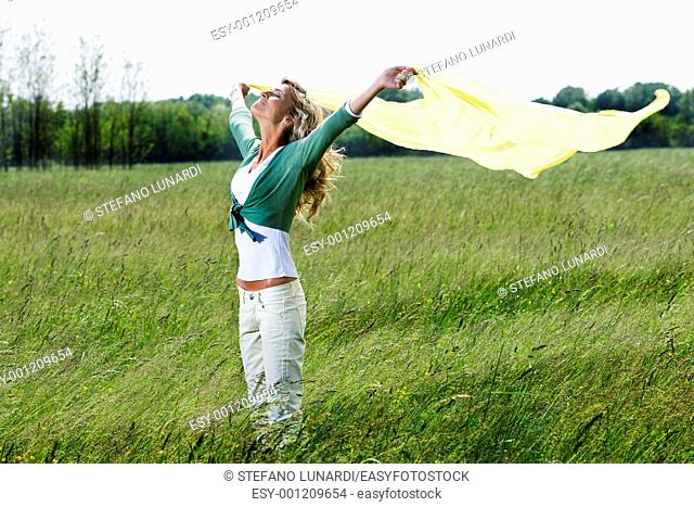 Young woman playing with yellow drape outdoors