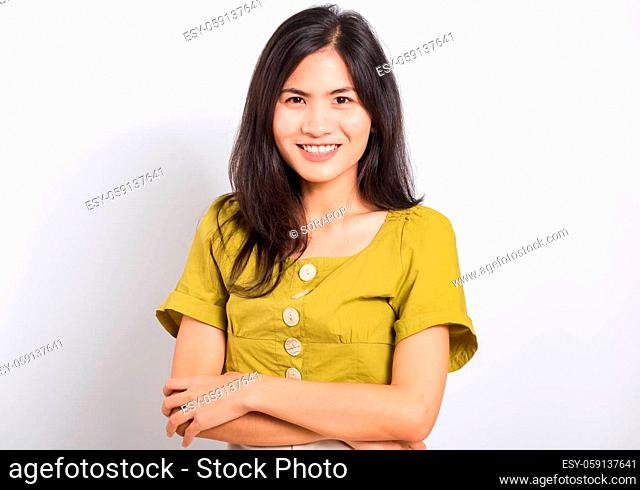 Portrait Asian beautiful young woman standing smile seeing white teeth, She crossed her arms and looking at camera, shoot photo in studio on white background