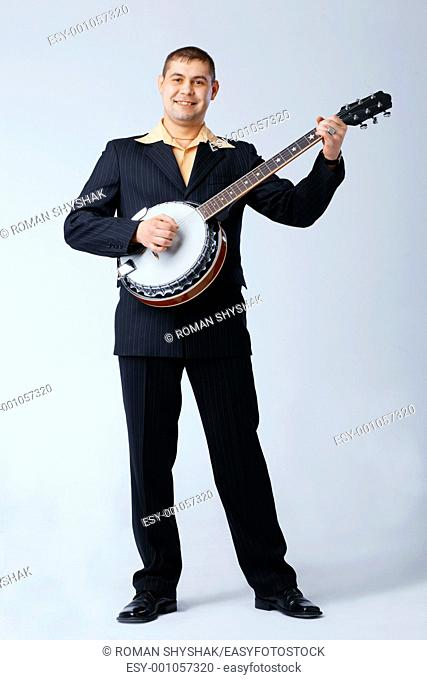 Man in suite is standing and playing on banjo against white, full length
