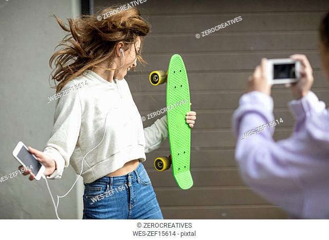 Friend taking picture of carefree teenage girl dancing while holding skateboard and listening to music