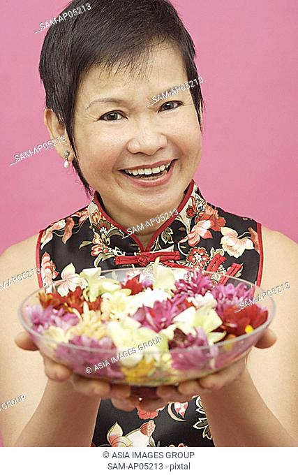 Mature woman holding bowl of flowers, smiling
