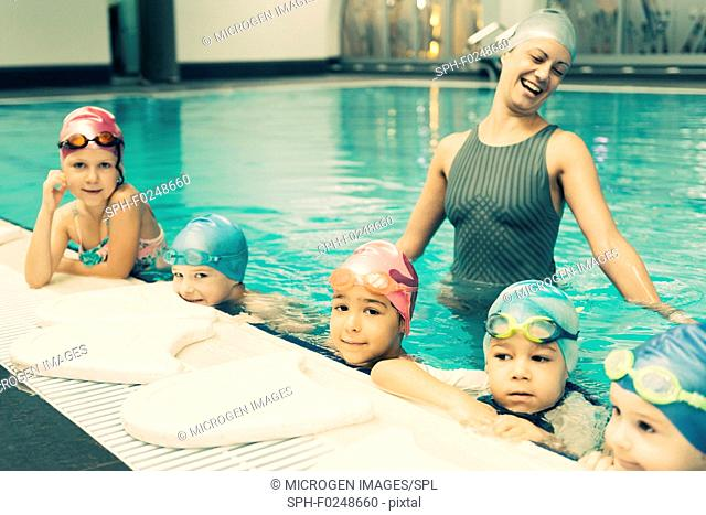 Swimming school for children. Group of children with swimming instructor