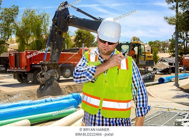 Caucasian construction worker listening to walkie-talkie