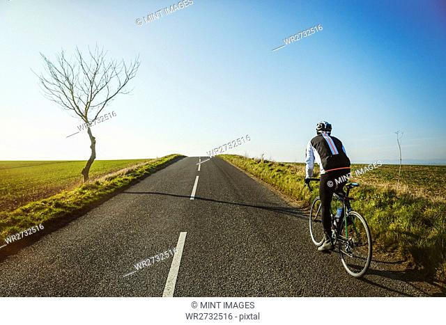 A cyclist riding along a country road on a clear sunny winter day