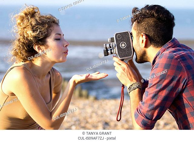 Young man filming woman with vintage camera