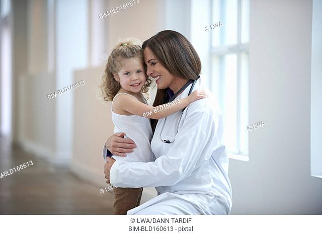Caucasian doctor and girl hugging in hallway
