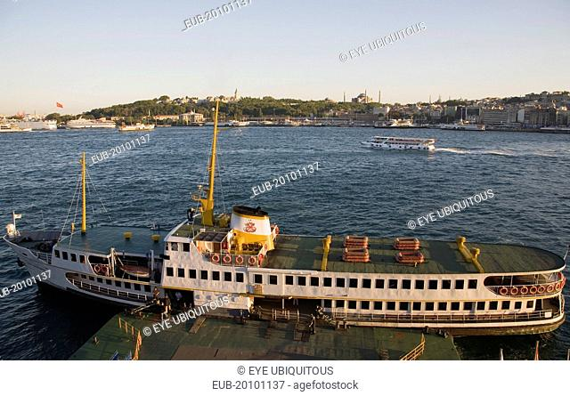 Sultanahmet. Bosphorous passenger ferry moored at sunset with the Hagia Sophia behind