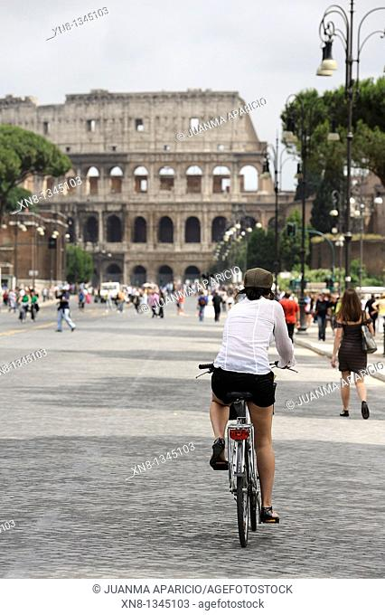 Young woman riding a bicycle to the Roman Colosseum, Rome, Italy