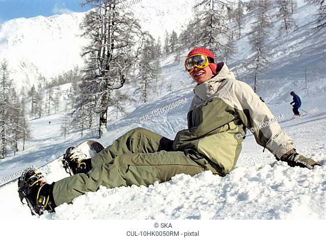 Boy sitting in snow with a snowboard