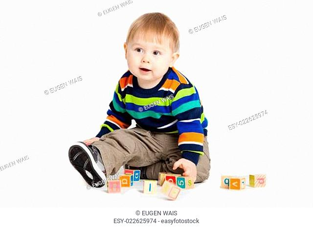baby playing with wooden toy cubes with letters. Wooden alphabet blocks