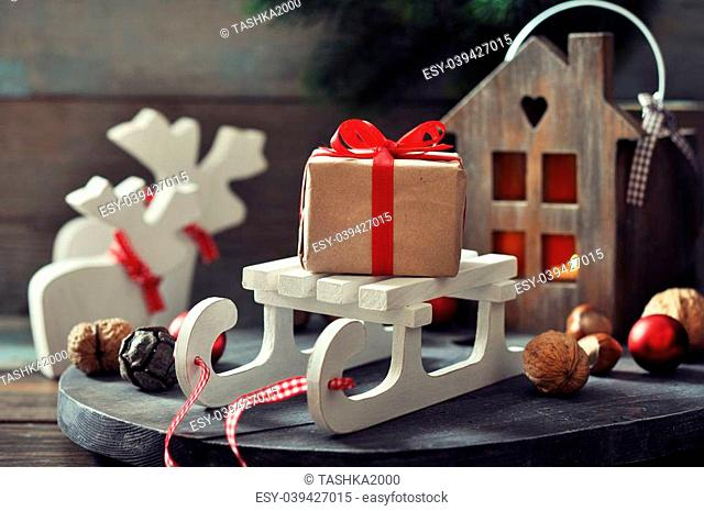 Christmas decorations with gift box on sled and lantern on wooden background