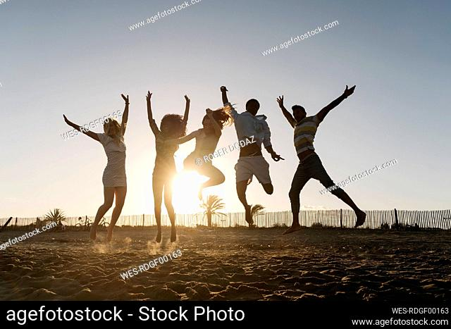 Friends jumping with joy on beach during sunset