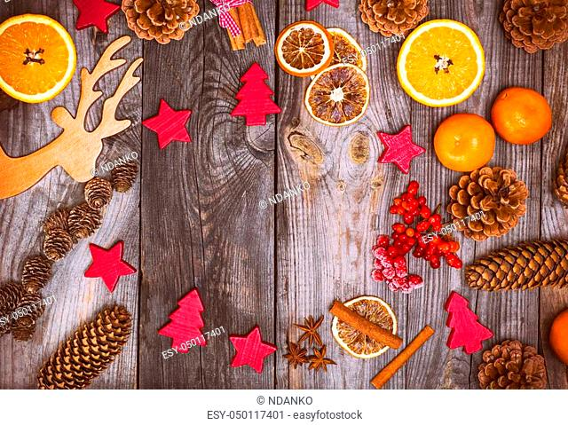 Christmas wooden background with cones and toys, empty space in the middle