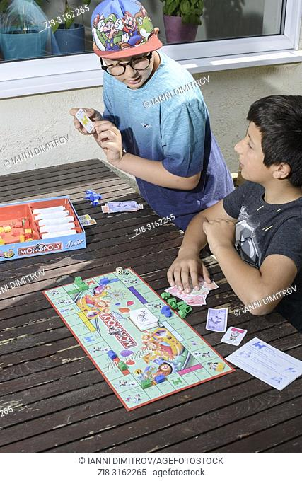 Boys playing together- monopoly board game,UK