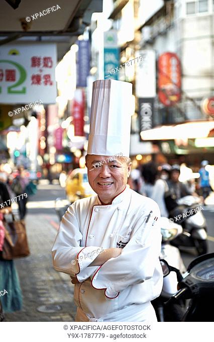 Head Chef Huang Lai Fa of The Grand Formosa Regent Hotel Taipei, posing and sampling food on Yongkang Street in Taipei, Taiwan