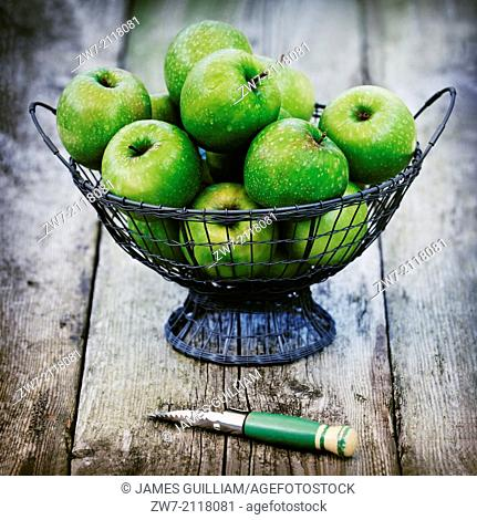 Fresh green apples variety Granny Smith in a wire basket on a weathered wooden table
