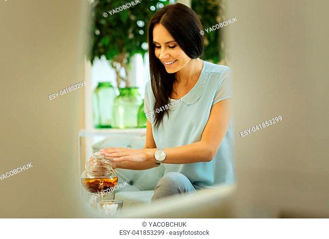 Favourite drink. Nice happy woman smiling while pouring tea