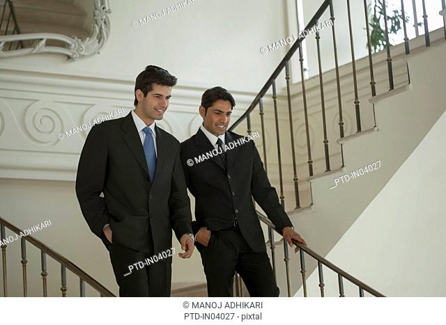 India, Two businessmen walking down stairs