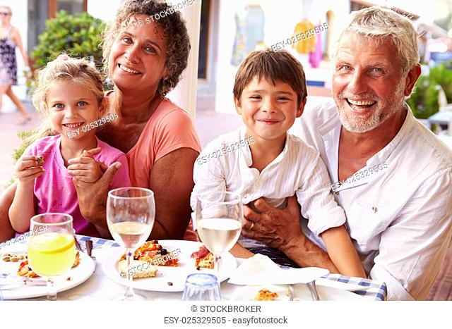 Grandparents With Grandchildren Eating Meal At Restaurant