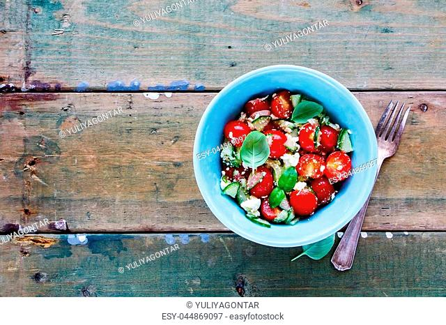 Healthy salad bowl with fresh summer vegetables and feta cheese on grunge wooden background. Weight loss clean eating, vegan, vegetarian, healthy