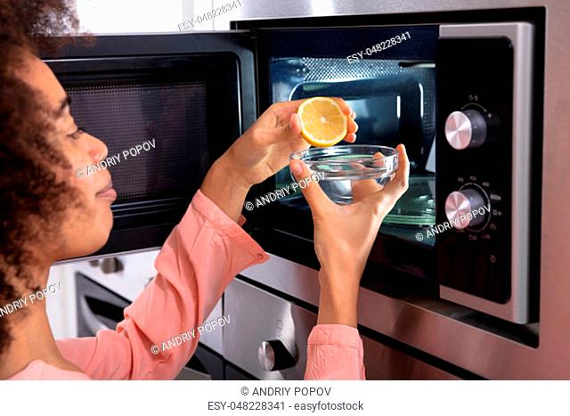 Woman's Hand Squeezing Halved Lemon In The Glass Bowl Near An Open Microwave Oven