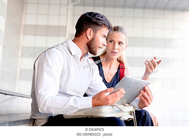 Mature man and woman sitting on steps, looking at digital tablet