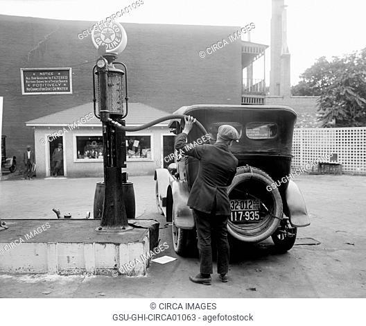 Man Putting Gas in Car at Gas Station, Washington DC, USA, circa 1920