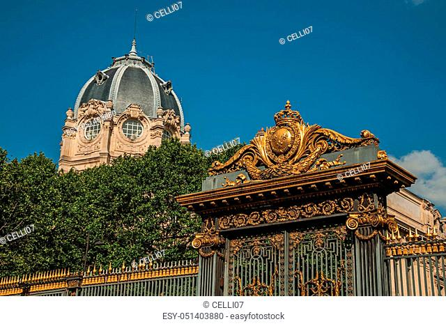 Golden iron gate lavishly decorated and dome under sunny blue sky in Paris. Known as the? City of Light?, is one of the most impressive world's cultural center
