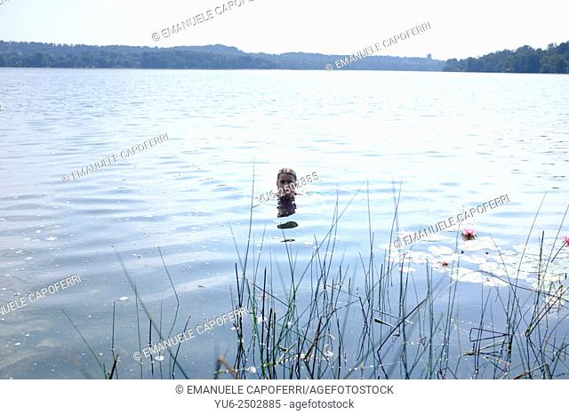 Girl takes a bath in Lake Monate, Cadrezzate, Lombardy, Italy