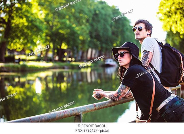 Young couple Garonne edge contemplates the banks