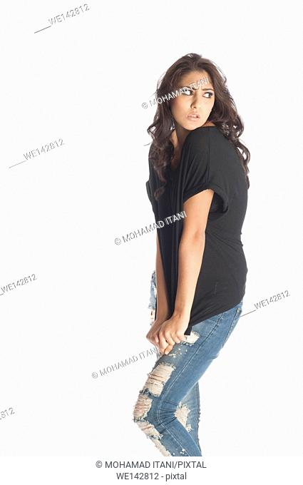 Serious young woman wearing ripped jeans
