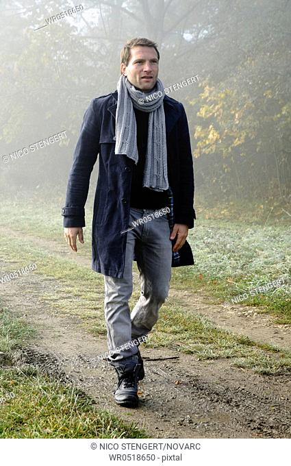 Man wearing autumnal clothes going nonchalantly along a forest path, men's fashion, fall