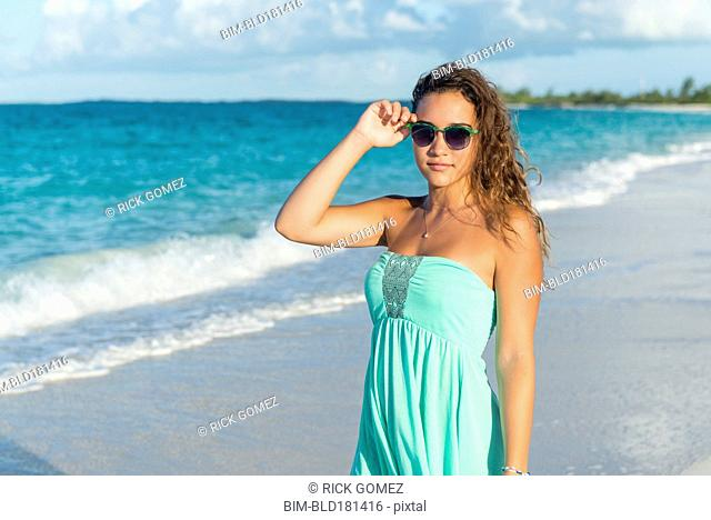 Hispanic teenage girl standing on beach