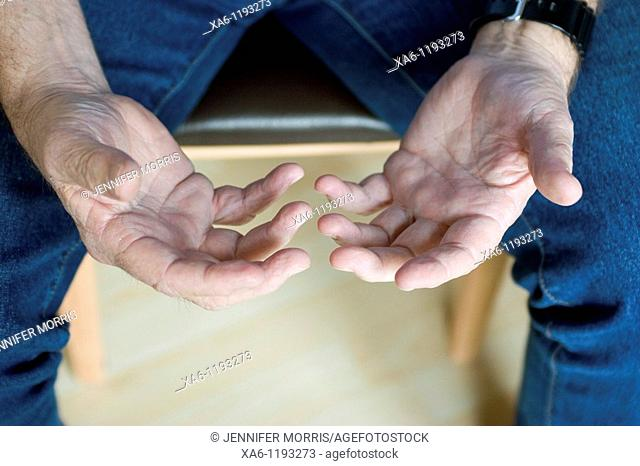 A middle-aged man's hands, open in his lap