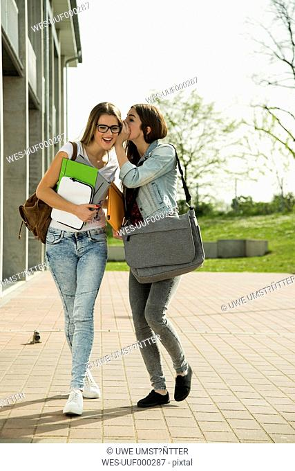 Two happy young students walking outdoors