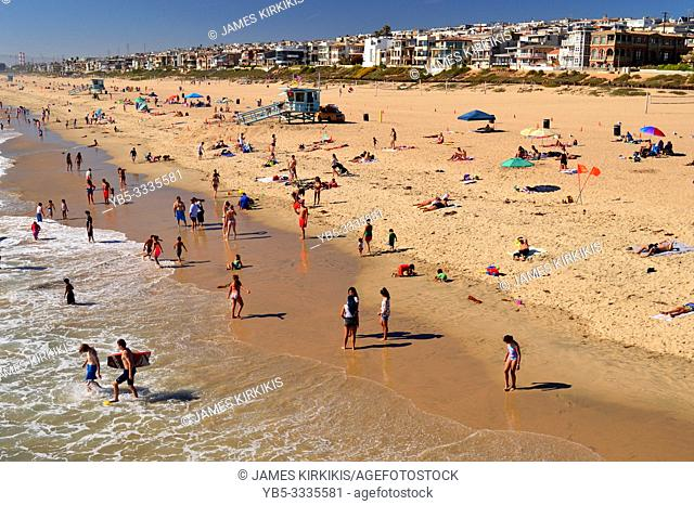 Beach goers enjoy the summer sun along the coast in Manhattan Beach, California