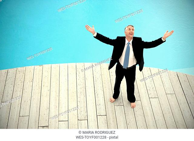 Barefoot businessman wearing black suit standing in front of swimming pool with arms raised