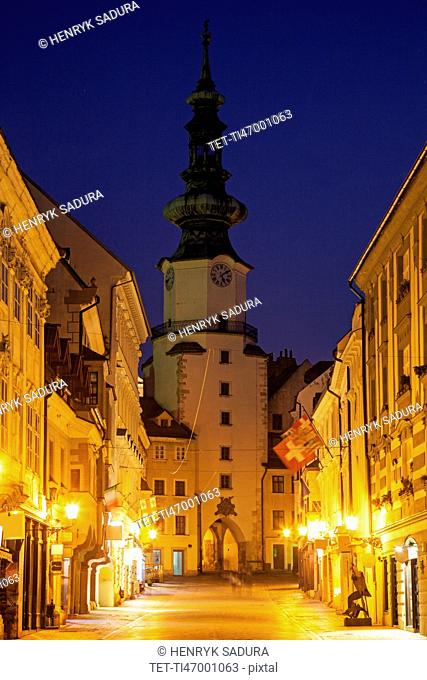 Illuminated alley and tower at night