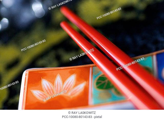 Red chopsticks laid upon a colorful plate