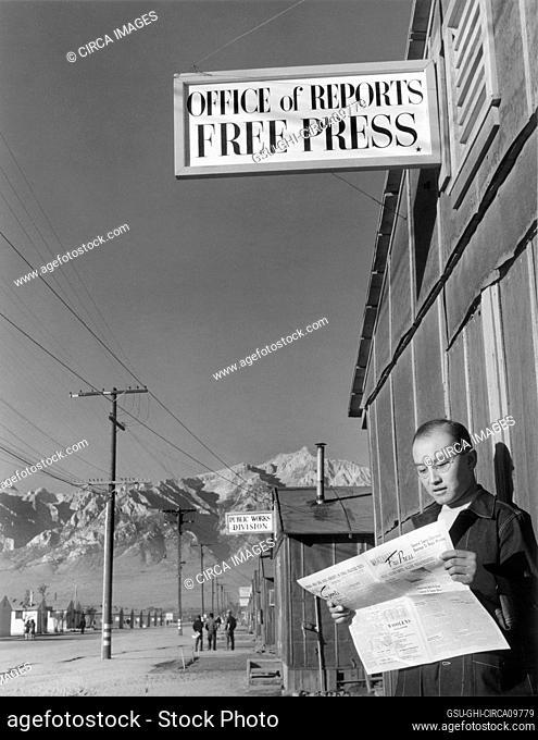 Editor Roy Takeno reading Copy of Manzanar Free Press in front of Newspaper Office, Manzanar Relocation Center, California, USA, Ansel Adams