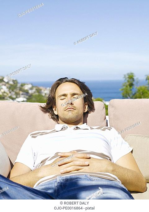 Man sleeping on sofa outdoors